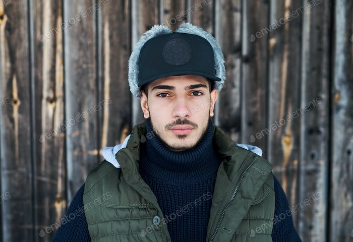 Young man with cap standing against wooden background outdoors in winter.