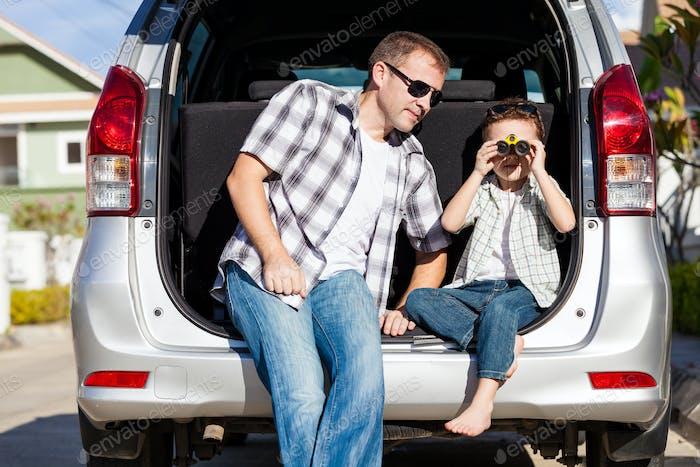 Glücklicher Vater und Sohn machen sich bereit für Roadtrip an einem sonnigen Tag.