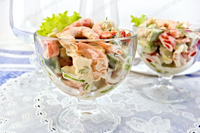 Salad with shrimp and tomatoes in glass on napkin
