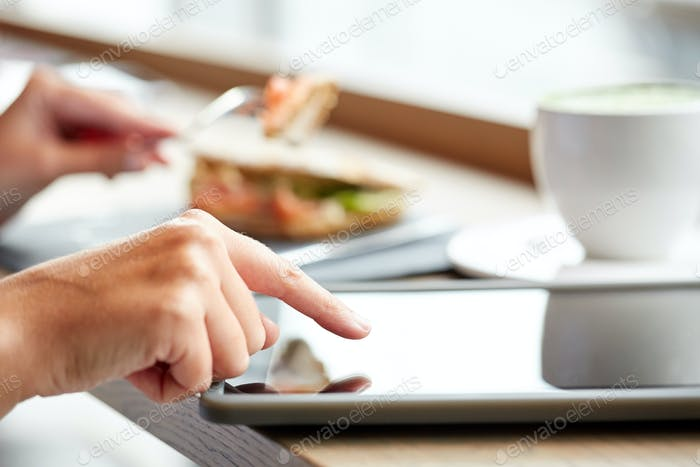 woman with tablet pc and panini sandwich at cafe