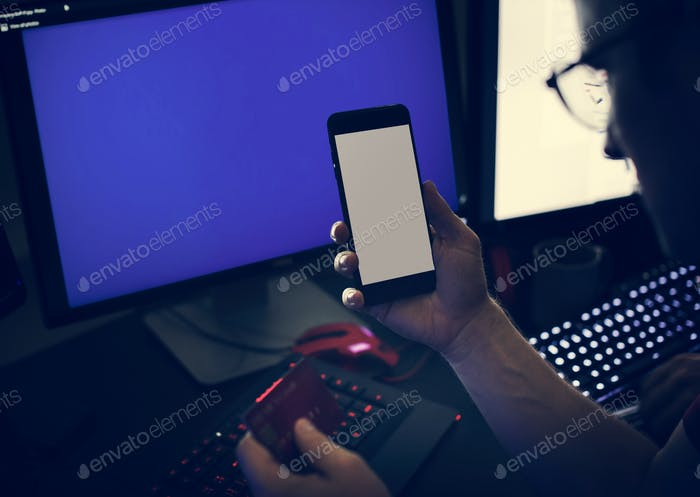 Closeup of hands holding mobile phone with computer laptop background