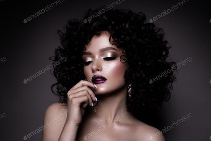 Glamour Dame, Schönes Mädchen auf grauem Hintergrund. Porträt. Welliges Haar, perfektes Make-up. Geschlossene Augen.