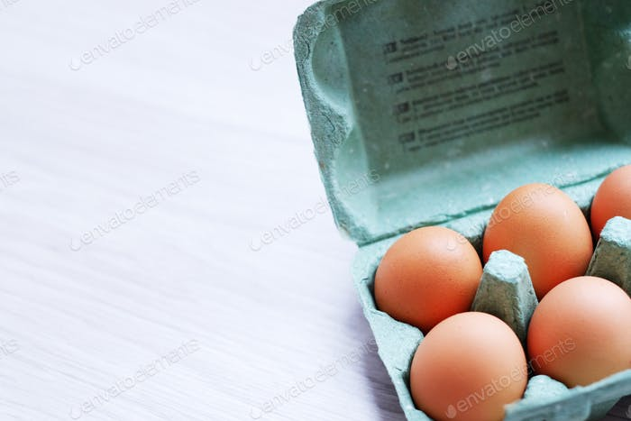Rustic food. Six chicken eggs in a paper crate on a table