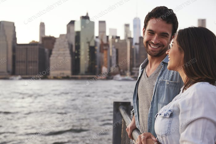 Young couple standing on quayside, side view
