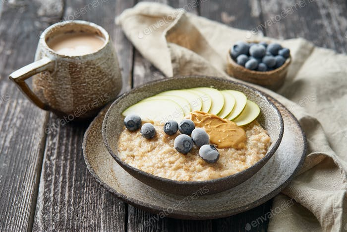 Oatmeal, healthy porridge in large bowl with fruits and berry for breakfast