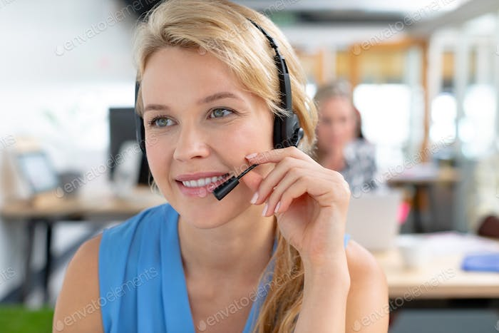 Beautiful Caucasian female customer service executive talking on headset