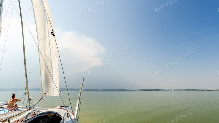 Girl on catamaran boat swims through Neusiedlersee lake panorama