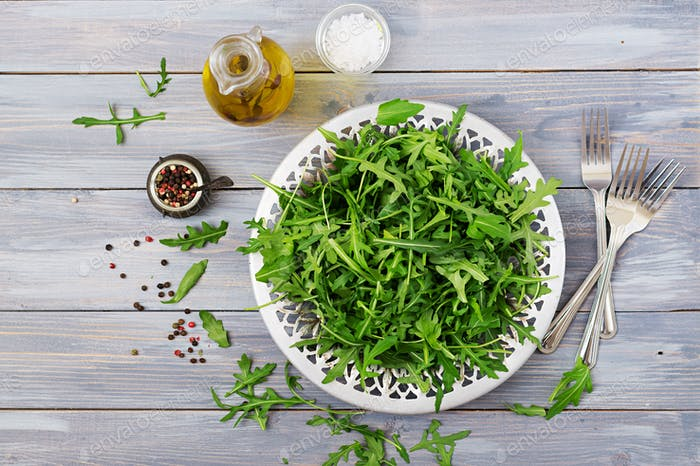 Fresh leaves of arugula in a bowl on a light wooden background. Flat lay. Top view