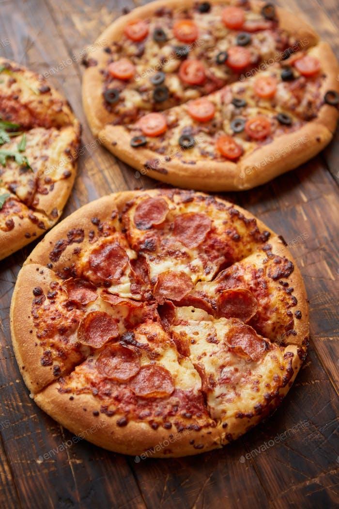Zusammensetzung von drei verschiedenen Arten Pizzen auf Holztisch