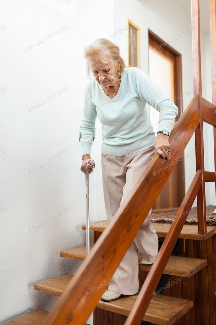 Ältere Frau zu Hause mit einem Stock, um die Treppe hinunter