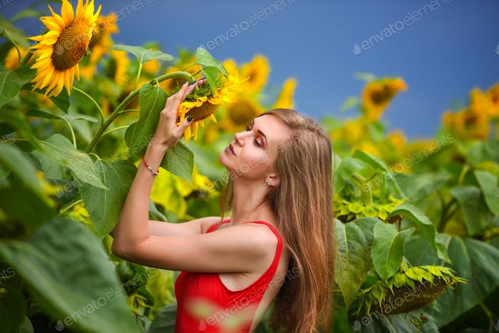 Portrait of beautiful girl in field with sunflowers