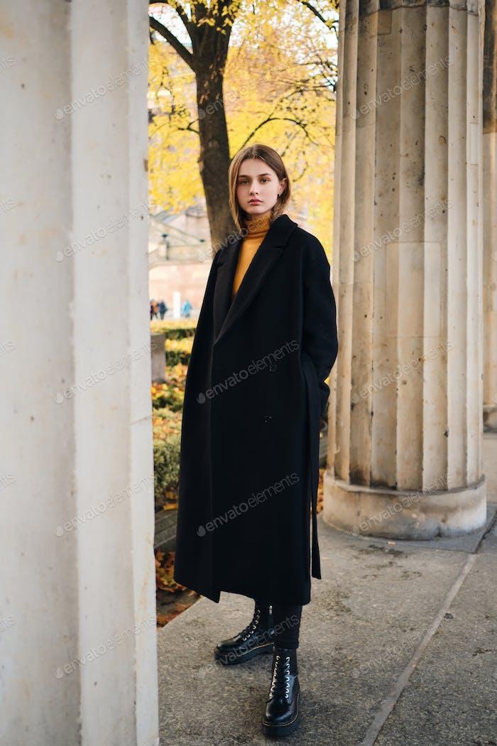 Attractive girl in black coat intently looking in camera outdoor