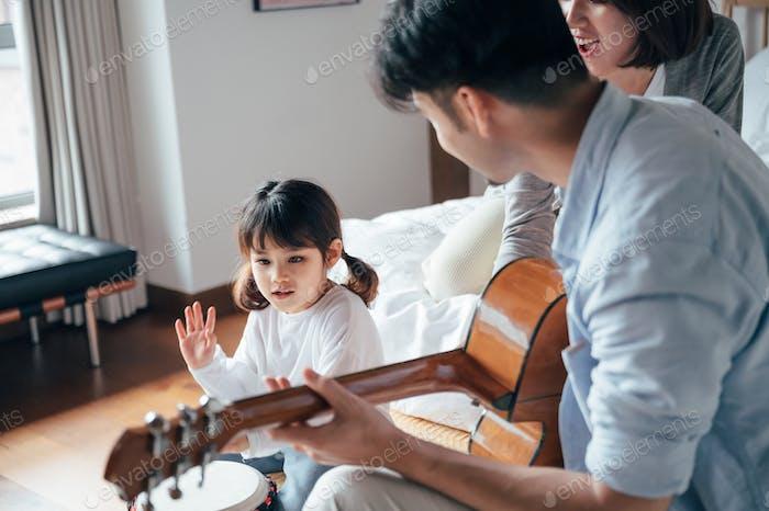 Glückliche Familie Spielinstrumente im Schlafzimmer