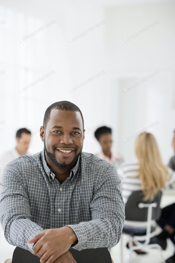 Un hombre sentado por separado de un grupo de personas sentadas alrededor de una mesa. Una reunión de negocios.