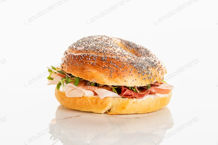 Fresh Delicious Bagel With Prosciutto on White Background