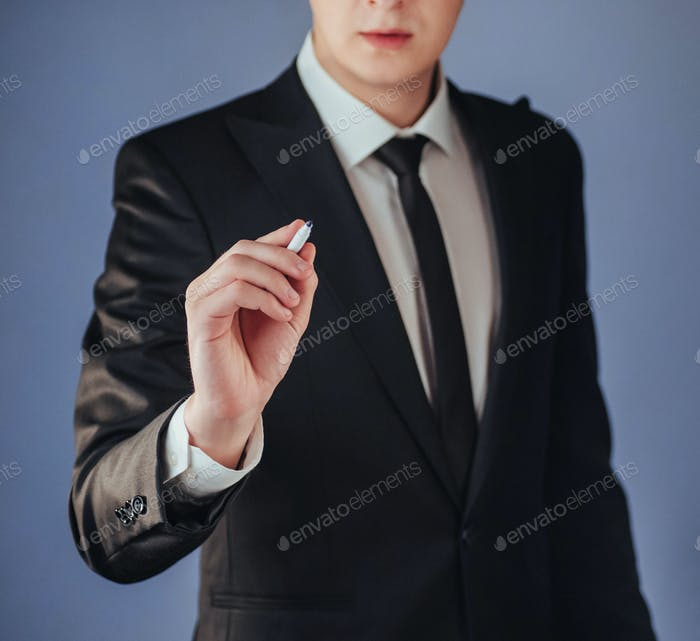 businessman in black suit writing something on board with marker