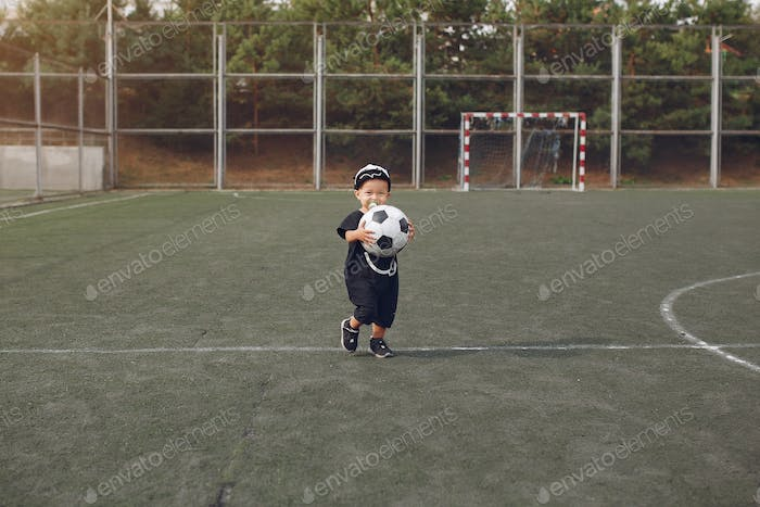 Little boy playing a football in a sports ground