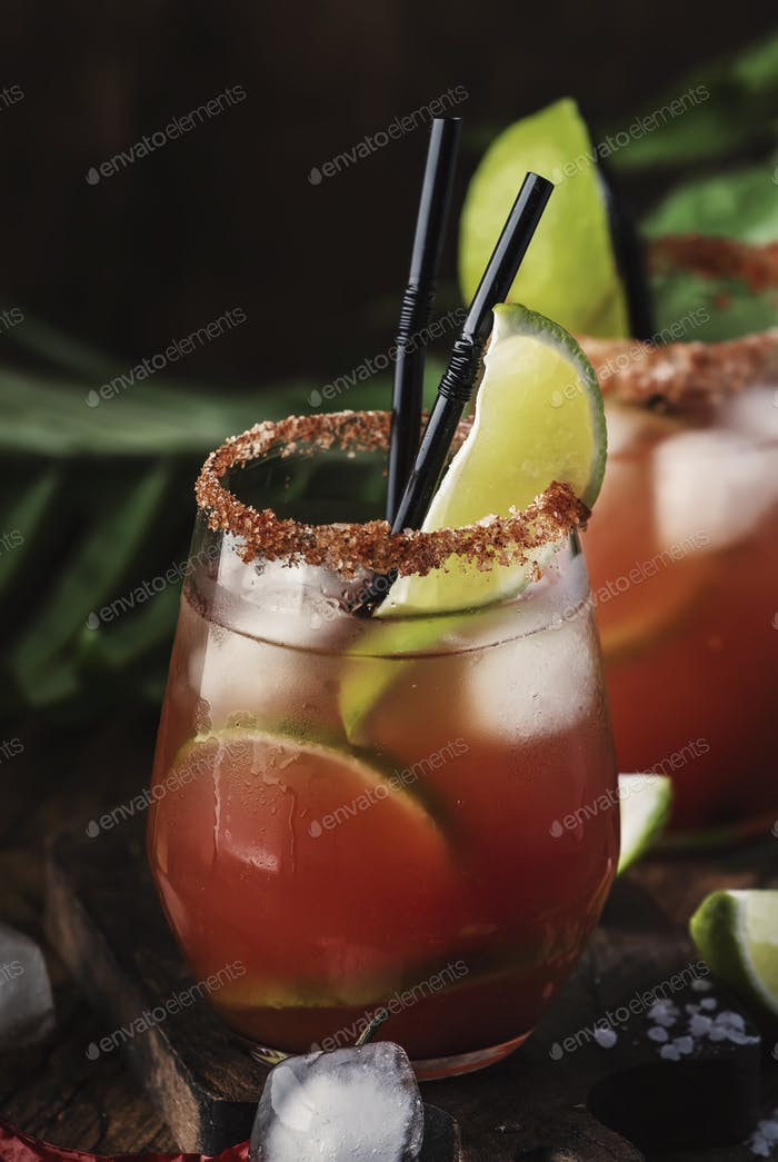 bloody mary alcoholic cocktail with beer, lime juice, tomato juice, spicy sauce and spices