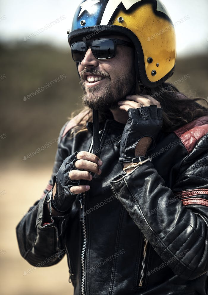 Bearded man wearing black leather jacket and sunglasses adjusting his yellow open face crash helmet.