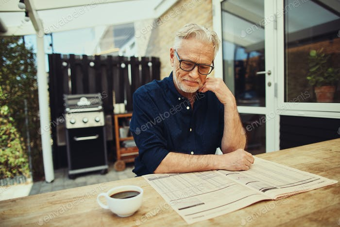 Senior man drinking coffee and reading a newspaper outside