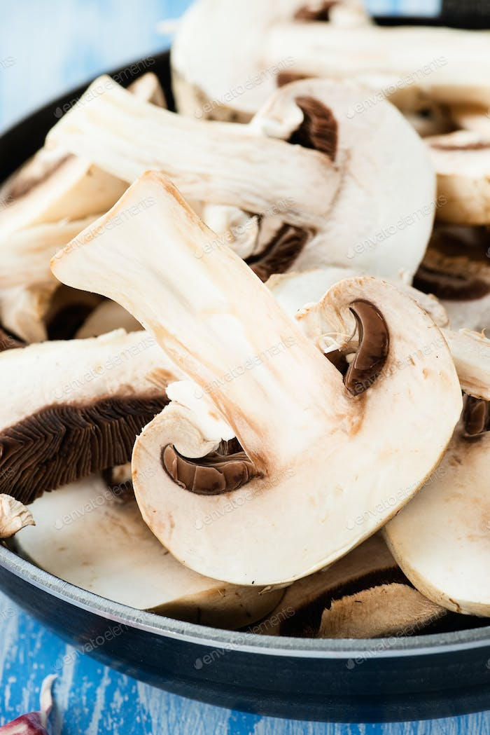 Fresh sliced button mushrooms in skillet