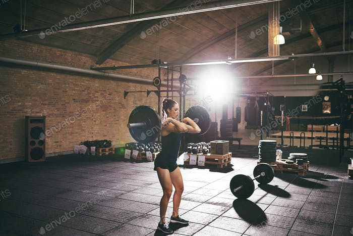 Young muscular woman training with heavy barbell