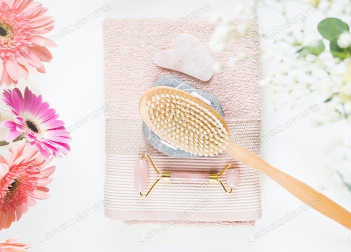 Massagebürste, Stein, Face Roller auf rosa Handtuch