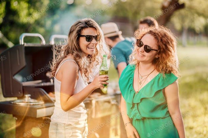 Cerca hasta retrato de las niñas bebiendo y riendo en patio trasero barbacoa parte