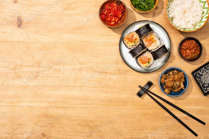 Top View of Bowls With Tasty Korean Side Dishes Near Chopsticks And Gimbap on Wooden Surface