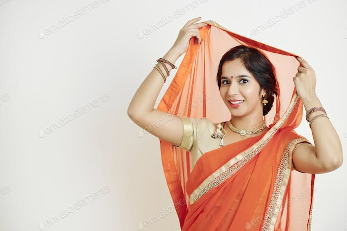 Woman putting on silk orange sari