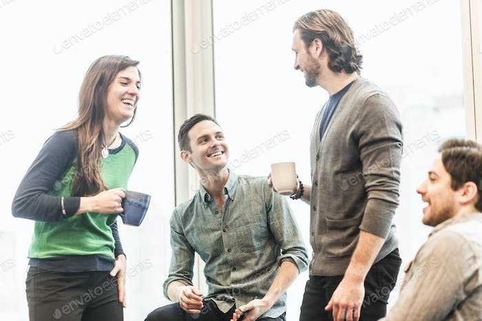 Four work colleagues on a break, laughing together.