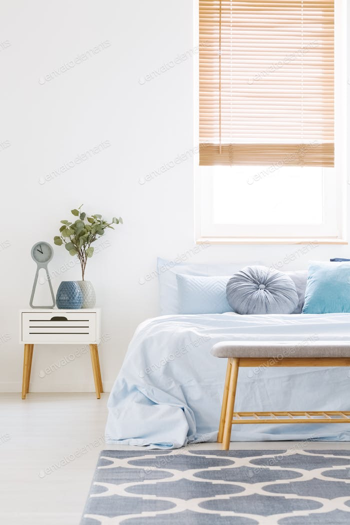 Window with wooden blinds in white bedroom interior with bed wit