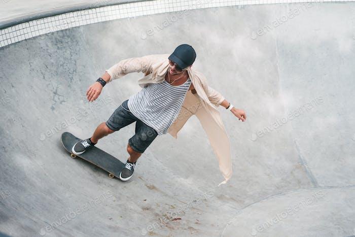 young skater skating on longboard in pool at skatepark