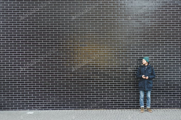 Young stylishly dressed man in winter clothes standing on a blank wall of black tiles.