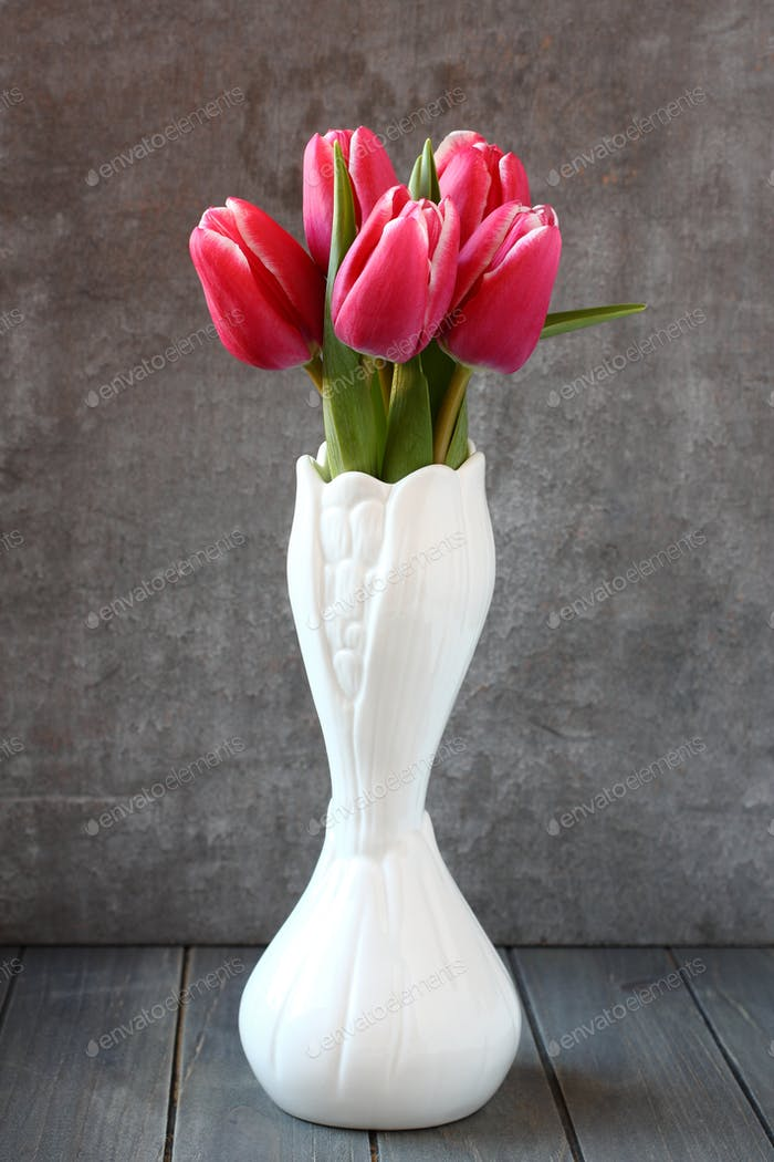 Bouquet of pink tulips in white vase on wooden background