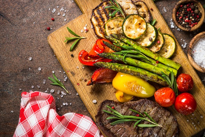 Beef steak grilled with vegetables on cutting board