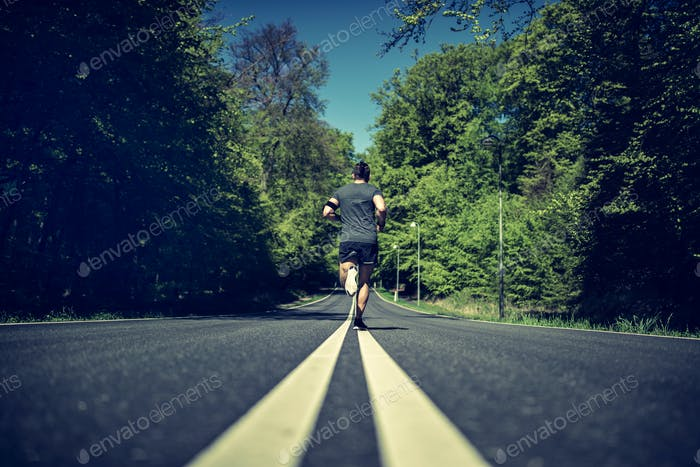 Fit young man in sportswear running down a country road