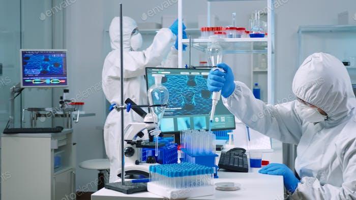 Scientist wearing coverall examining drug discovery with micropipette