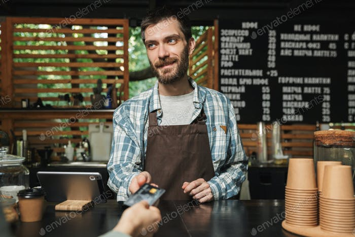 Portrait of happy barista man taking credit card from customer w