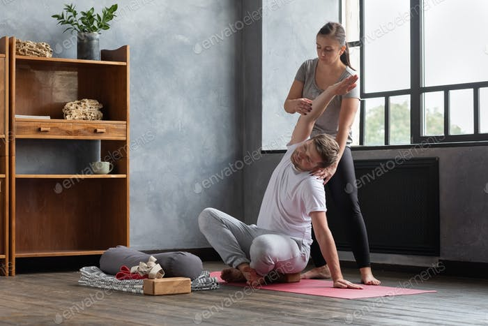 Man practicing yoga with instructor, sitting in Sukhasana, doing Easy Seat pose