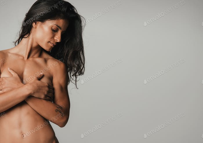 Nude young woman covering her breasts