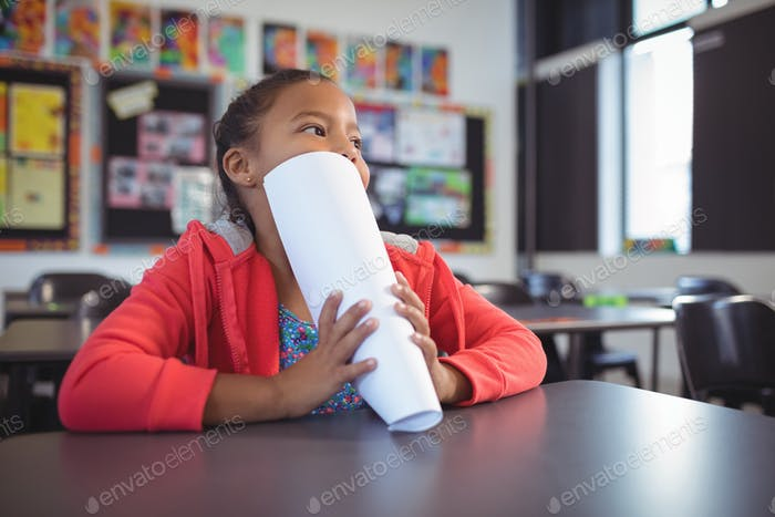Thoughtful girl covering face with papers while sitting at desk