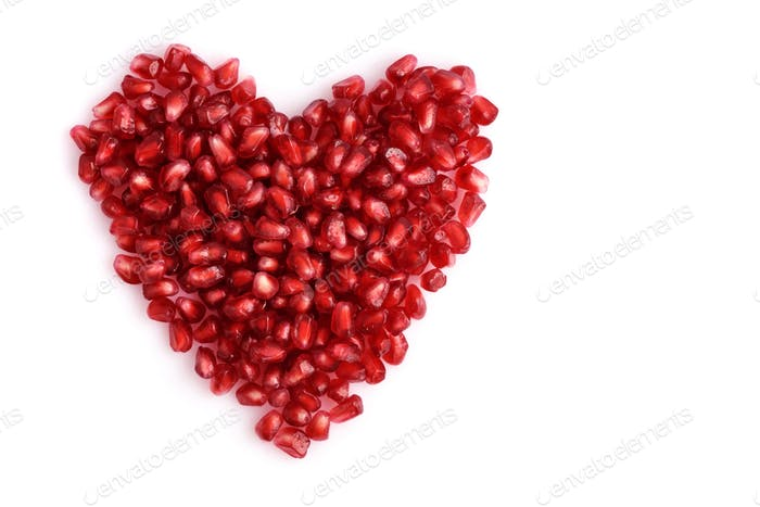 Pomegranate seeds on white background. Heart shape