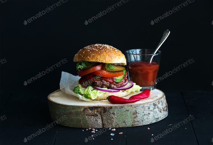 Fresh homemade burger on wooden serving board with spicy tomato sauce, sea salt and herbs