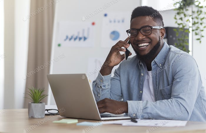 Cheerful Entrepreneur Speaking On Mobile Phone While Working In Office