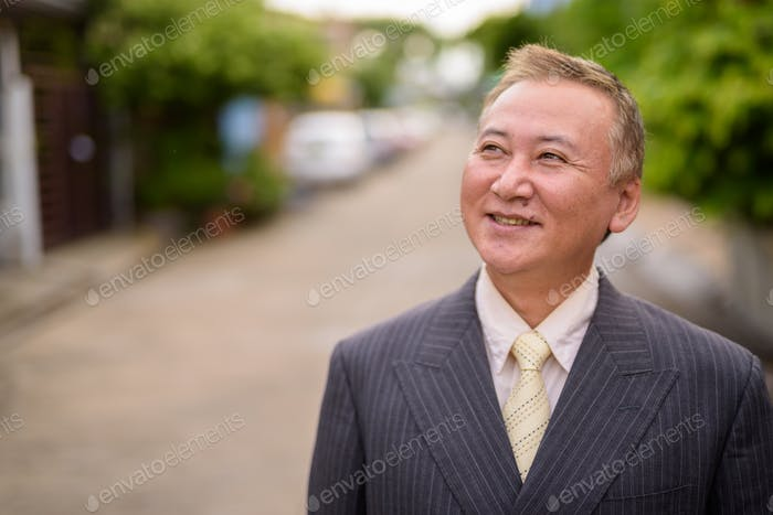 Mature Asian businessman in the streets outdoors