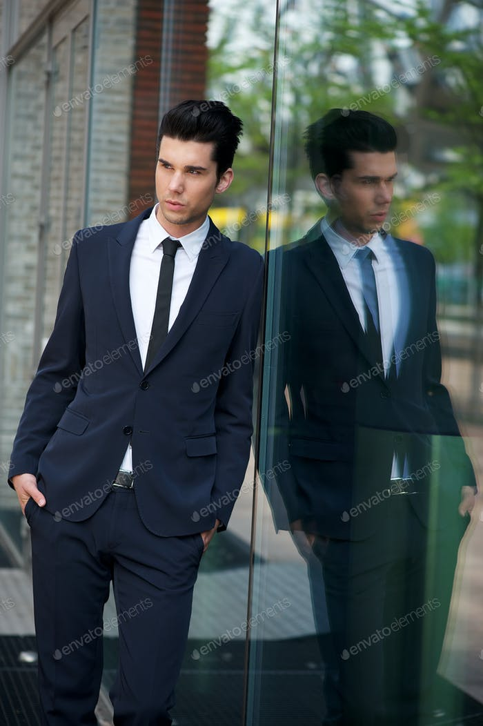Handsome businessman leaning against glass building