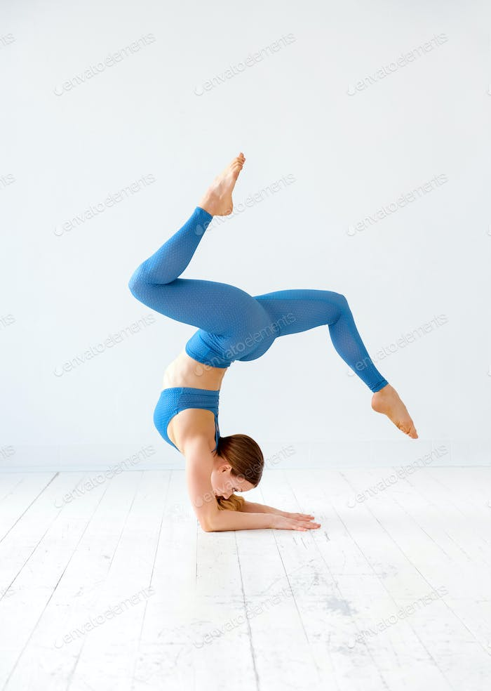 Sporty young woman doing an elbow stand