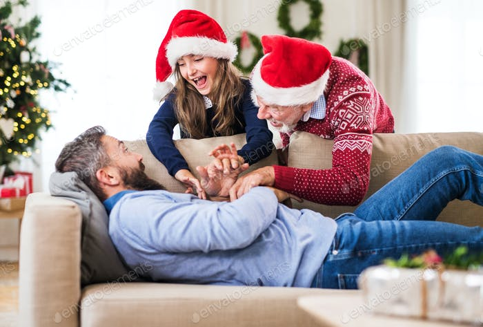 A small girl with grandfather waking up her sleeping father at Christmas time.