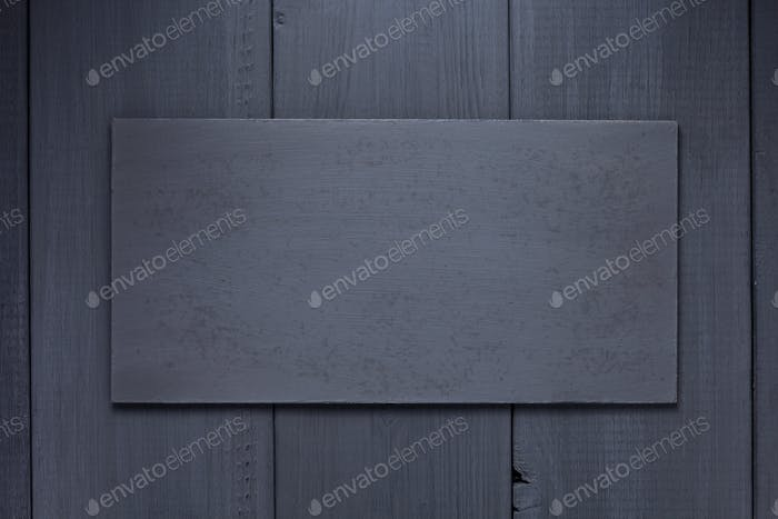nameplate or wall sign at black wooden background texture